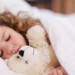 Girl sleeping with her teddy — Stock Photo #11210215