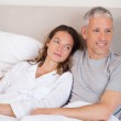 Portrait of a happy couple lying on a bed — Stock Photo #11210321
