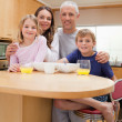 Stock Photo: Portrait of a smiling family having breakfast