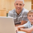 Young boy and his father using a laptop — Stock Photo #11210503