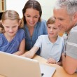 Lovely family using a notebook — Stock Photo