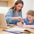 Woman helping her daughter doing her homework — ストック写真