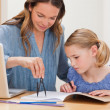 Mother helping her daughter doing her homework — Foto Stock