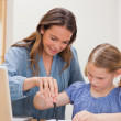 Portrait of a mother helping her daughter doing her homework — Stock Photo