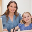 Portrait of a beautiful woman helping her daughter doing her hom — Foto Stock