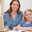 Beautiful woman helping her daughter doing her homework — ストック写真