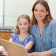 Foto Stock: Portrait of a girl doing her homework while her mother is workin