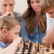 Focused children playing chess in front of their parents — Stock Photo