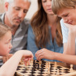 Close up of siblings playing chess in front of their parents — Stock Photo