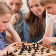 Close up of children playing chess in front of their parents — Stock Photo