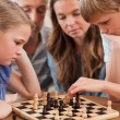 Stock Photo: Close up of serious children playing chess in front of their par