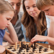 Close up of serious children playing chess in front of their par — Stock Photo