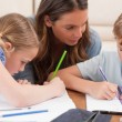 Mother helping her children to do their homework — Stock Photo