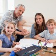 Stock Photo: Happy parents helping her children to do their homework