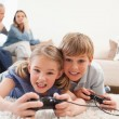 Cheerful children playing video games with their parents on the — Stock Photo #11210675