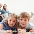 Playful children playing video games with their parents on the b — Stock Photo