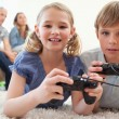 Playful siblings playing video games with their parents on the b — Stock Photo