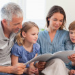 Family reading a book together — Stock Photo #11210689