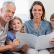 Happy family reading a book together — Stock Photo