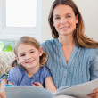 Stock Photo: Portrait of mother reading book to her daughter