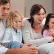 Cheerful family watching television together - Stock Photo