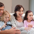 Stock Photo: Cheerful family playing video games together