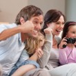 Stock Photo: Positive family playing video games together