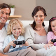 Stock Photo: Smiling family playing video games together