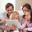 Stock Photo: Delighted family using tablet computer