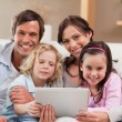 Charming family using a tablet computer — Stock Photo #11210739