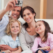 Portrait of a happy father taking a picture of his family - Stock Photo