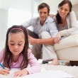 Little girl drawing with her parents in the background — Stock Photo #11210757