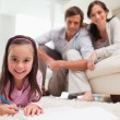 Cute girl drawing with her parents in the background — Stock Photo #11210758