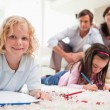 Children drawing while their parents are in the background — Stock Photo