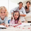 Stock Photo: Cute siblings drawing while their parents are in the background