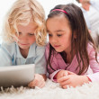 Children using a tablet computer while their parents are in the — Stock Photo