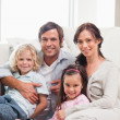Portrait of a family relaxing on a sofa — Stock Photo #11210778