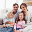 Family relaxing on a sofa — Stock Photo #11210780