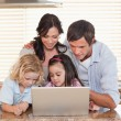 Family using a notebook together — Stock Photo