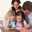 Happy family using a tablet computer together — Stock Photo #11210804