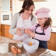 Portrait of a mother and her happy daughter baking — Stock Photo