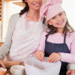 Portrait of a mother baking with her daughter — Stock Photo