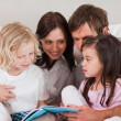 Family reading a book — Stock Photo