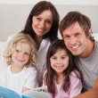 Portrait of a happy family reading a book — Stock Photo