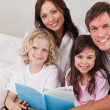 Happy family reading a book — Stock Photo
