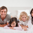 Smiling family lying in a bed — Stock Photo #11210914