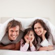 Portrait of parents lying under a duvet with their daughter — Stock Photo #11210931