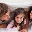 Cheerful family lying under a duvet — Stock Photo #11210935