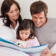 Happy parents reading a story to their daughter — Stock Photo