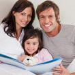 Royalty-Free Stock Photo: Smiling parents reading a story to their daughter